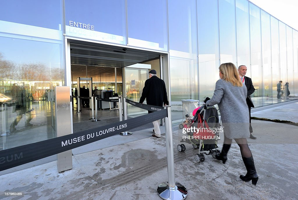 People enter the Louvre-Lens museum on December 8, 2012 in Lens, northern France. The Louvre museum opened a new satellite branch among the slag heaps of a former mining town on Dcember 4, 2012 in a bid to bring high culture and visitors to one of France's poorest areas.