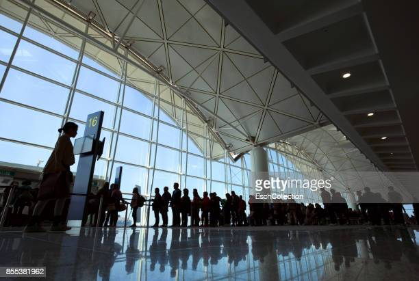 People entering airplane at gate of modern airport