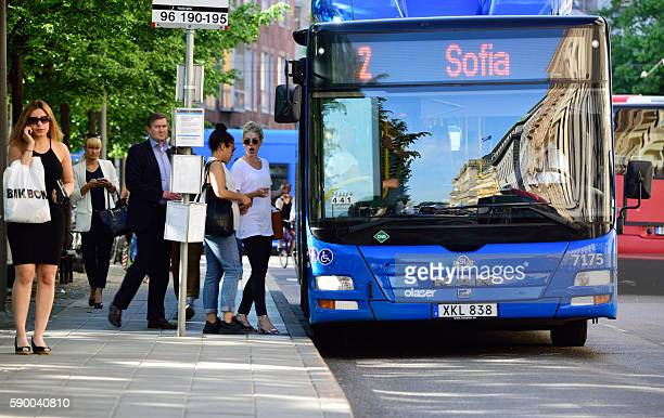 People entering bus at bus stop in Stockholm