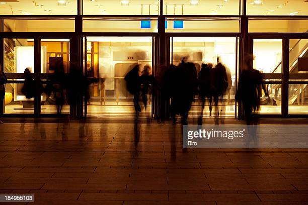 People Entering Modern Building at Evening