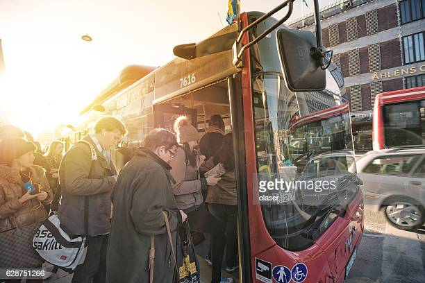 People enters bus at busstop
