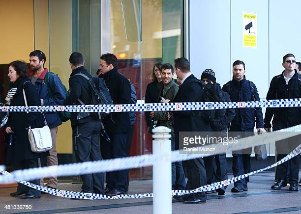 People enters the Australian Federal Police headquarters cordoned with police tape due to a suspicious package on July 20 2015 in Sydney Australia...