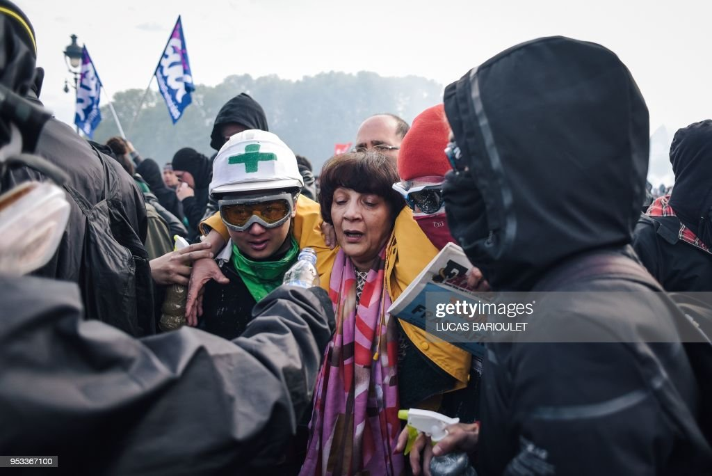 People escort a woman who cries after receiving tear gas, on Pont d'Austerlitz, during the annual May Day workers' rally in Paris on May 1, 2018. - Anti-capitalist protesters torched a McDonald's restaurant and clashed with police in Paris on the fringes of a May Day rally in Paris on May 1. Shouting slogans such as 'Rise up, Paris' and 'Everyone hates the police', over 1,000 youths with black jackets and face masks joined the traditional union-led demonstration for worker's rights, AFP journalists reported.