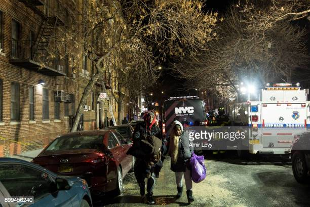 People evacuate from their house after a fatal major house fire on Prospect avenue on December 28 2017 in the Bronx borough of New York City Over 170...