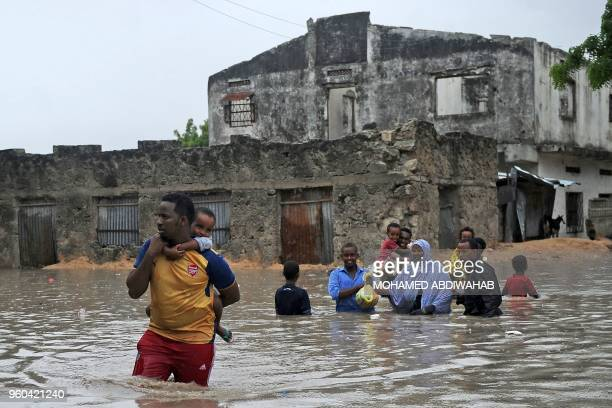 People evacuate their homes through waistdeep flood water in Mogadishu on May 20 2018 after homes were inundated in Somalia's capital following heavy...