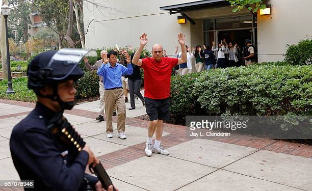 People evacuate with their hands up after a shooting on the UCLA campus on June 1 2016 in Los Angeles California The campus was placed on lockdown...