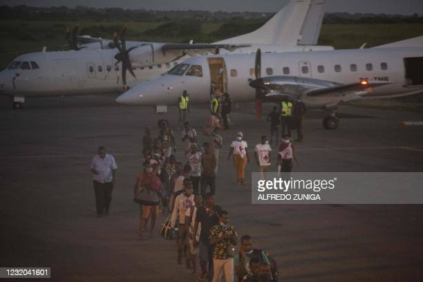 People evacuated from the city of Palma arrive on an humanitarian flight at the airport in Pemba on March 31, 2021. - More than 5,000 people have...