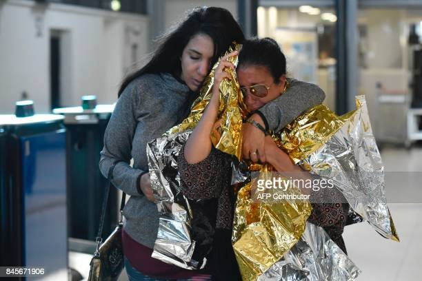 TOPSHOT People evacuated from the French Caribbean island of SaintMartin that was hit by Hurricane Irma react as they walk after landing at the...