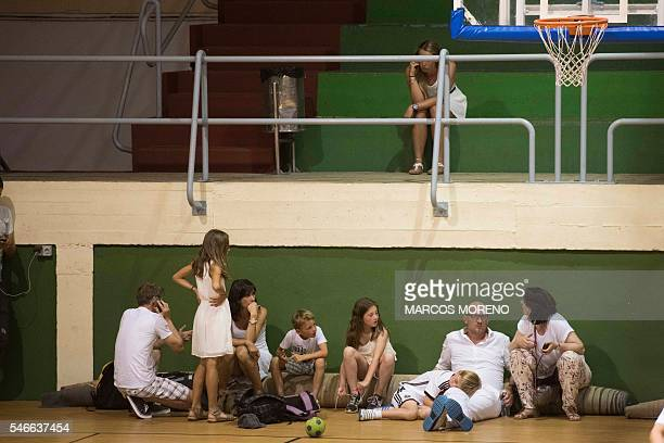 People evacuated from the seaside resort of Alcaidesa due to a wildfire take shelter at a sports complex in La Linea de la Concepcion province of...