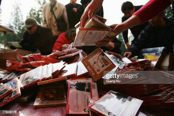 People examine pirated DVD disks at a book fair on November 2, 2007 In Beijing, China. More efforts are needed to raise awareness of intellectual...