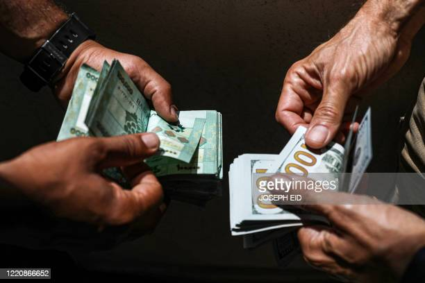 People exchange Lebanese pound and US dollar notes on the black market in Lebanon's capital Beirut on June 18 2020