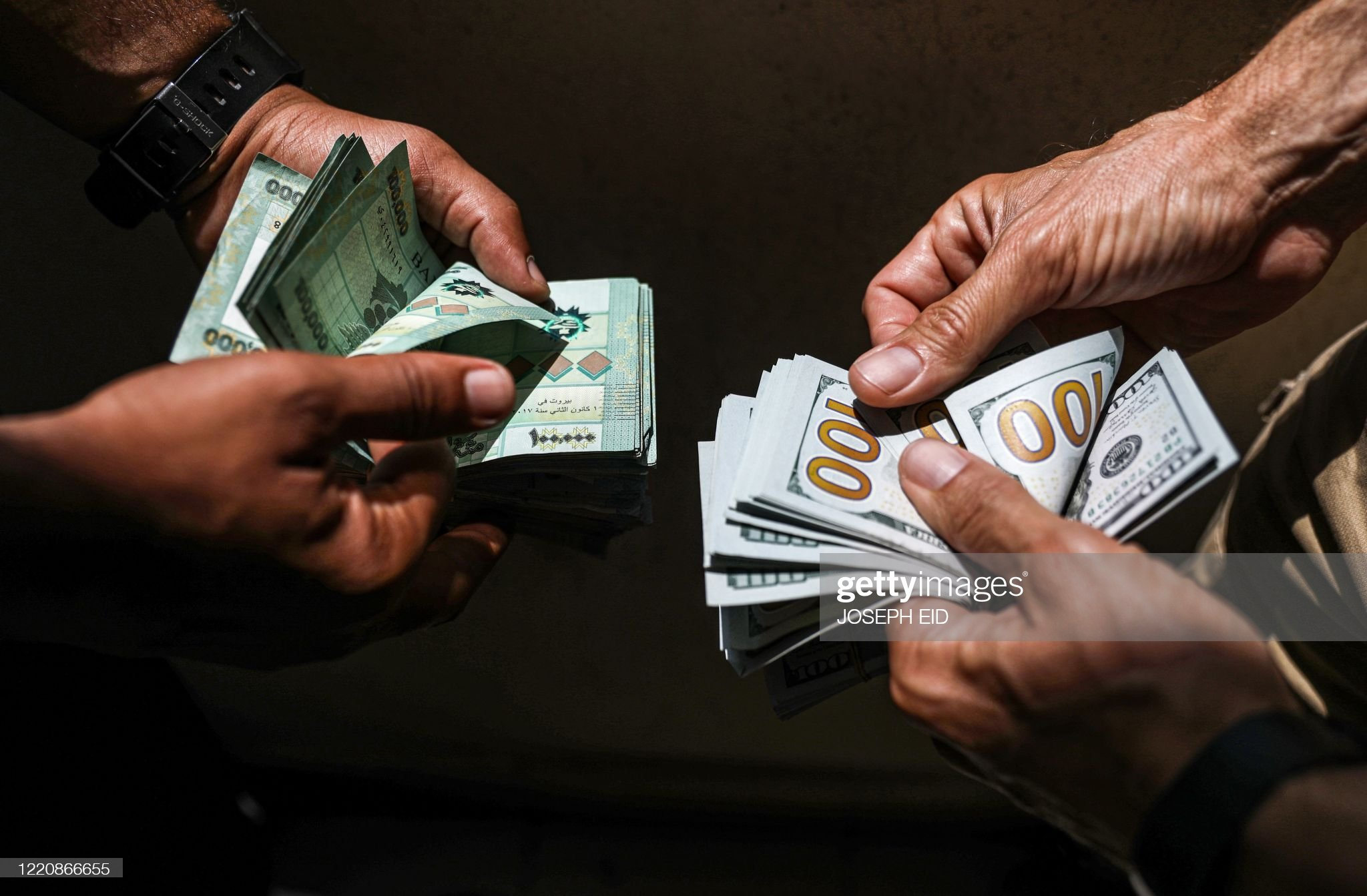 People exchange Lebanese pound and US dollar notes on the black market in Lebanon's capital Beirut on June 18, 2020. (Photo by JOSEPH EID / AFP)