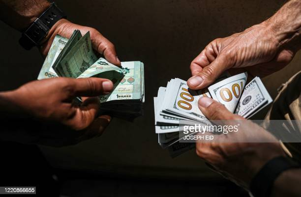 People exchange Lebanese pound and US dollar notes on the black market in Lebanon's capital Beirut on June 18, 2020.