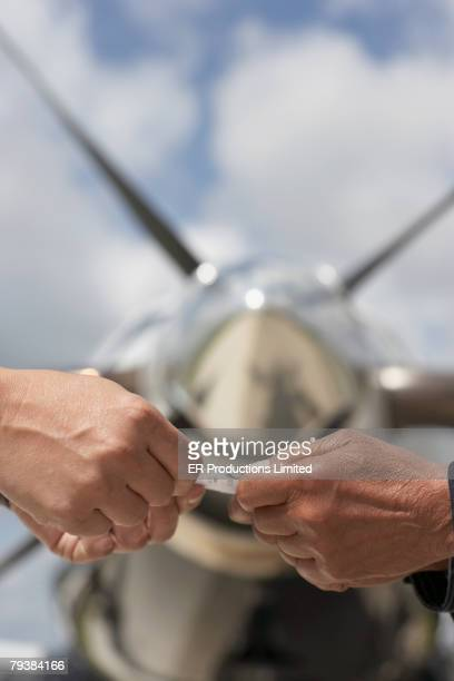People exchanging card in front of airplane