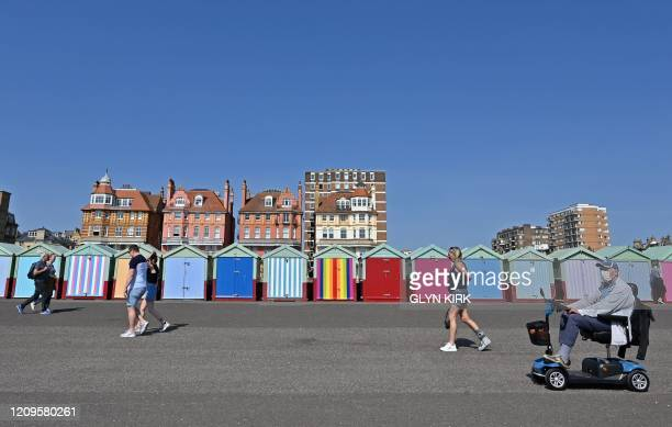 People exercise along the seafront in Brighton on the south coast of England on April 10 2020 as warm weather tests the nationwide lockdown and the...