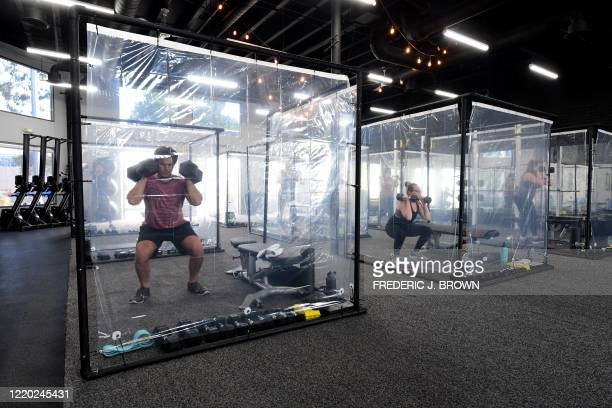 TOPSHOT People exercise at Inspire South Bay Fitness behind plastic sheets in their workout pods while observing social distancing on June 15 2020 in...