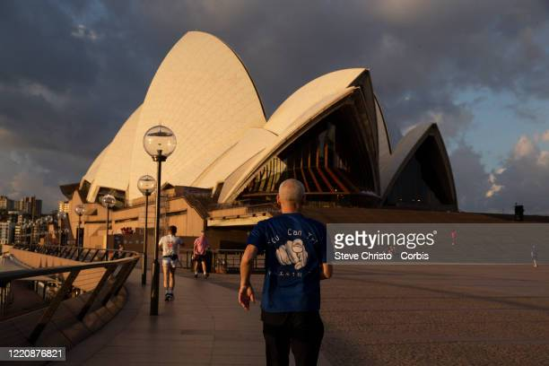 People exercise in self isolation in the Sydney Opera House predict on March 26, 2020 in Sydney, Australia. Further restrictions on travel and...
