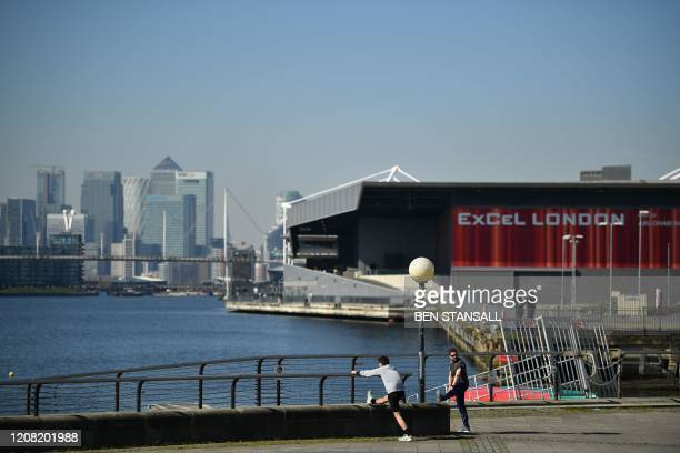 People exercise near the the ExCeL London exhibition centre in London on March 25 2020 that the government announced will be converted into a field...