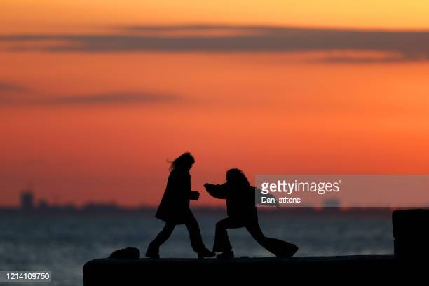 People exercise on the seafront after recent incidents of members of the public ignoring government advice on social distancing on March 22 2020 in...