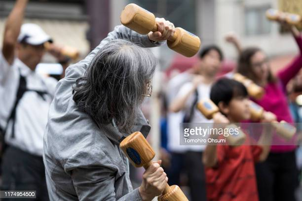 People exercise with wooden dumbbells during an event marking Respect for the Aged Day at a temple in the Sugamo shopping district on September 16...