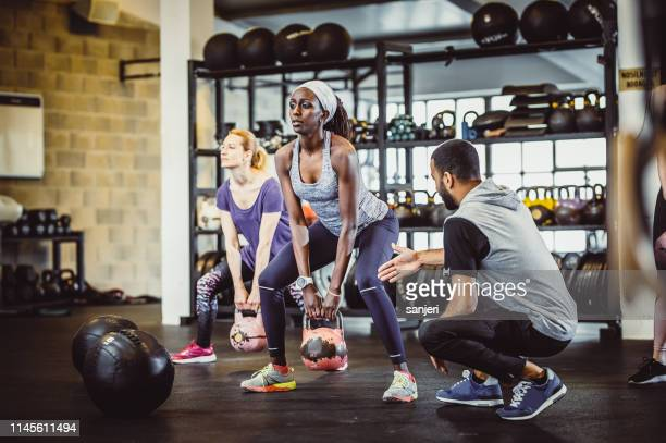 people exercising in a gym with medicine balls - fitness instructor stock pictures, royalty-free photos & images