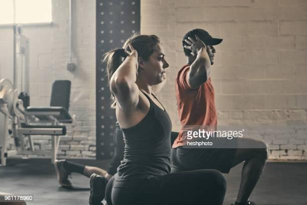 people exercising in gym, hands behind head lunging - heshphoto stock-fotos und bilder