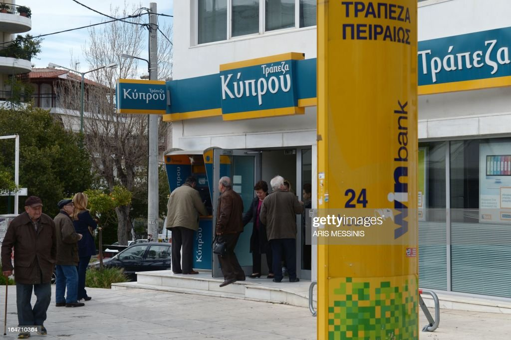 People exit a Bank of Cyprus branch in Athens on March 27, 2013, as Greek subsidiaries of three Cypriot banks reopened today after Greece's third lender, Piraeus bank, signed an agreement to acquire all their deposits, loans and branches. But banks in Cyprus itself remained closed as authorities worked out a plan to get them back up and running amid the country's financial crisis.