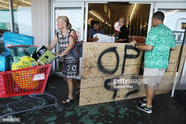 People exit a hardware store two days after Hurricane Irma swept through the area on September 12 2017 in Fort Myers Florida Hurricane Irma made...