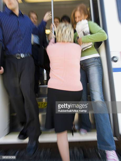 People exiting a passenger train while a woman tries to enter the train