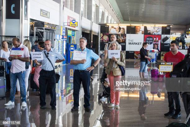 People expect the arriving passengers at the exit in Barcelona airport