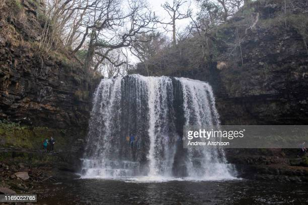 People explore and go behind the Sgwd Yr Eira Waterfall in the Afon Hepste River in Brecon Beacons Waterfall Country National Park, Wales, Powys,...