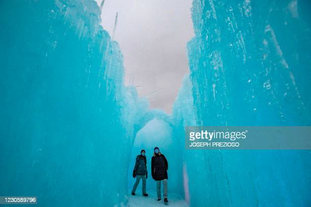 People explore the ice walls, tunnels and lights at Ice Castles in North Woodstock, New Hampshire, on January 14, 2021. - Hundreds of people attended...
