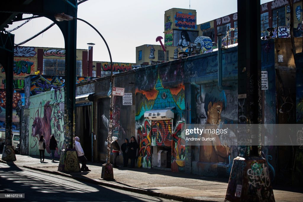 People explore the outside of the 5 Pointz Building, a landmark in the New York graffiti scene that has attracted artists from around the globe, on October 28, 2013 in the Long Island City neighborhood of the Queens borough of New York City. The artists that have been using 5 Pointz to paint for the past two decades are currently in a battle with the building's owners, who want to tear the building down to build apartment high rises worth $400 million. The 5 Pointz artistic community have also called on street artist Banksy who is currently in the midst of a high profile 'month in residence' series, creating work through out the streets of New York, to weigh in on the battle, though so far the artist has stayed silent. Meres One says he is prepared to chain himself to the building, should demolition move forward.