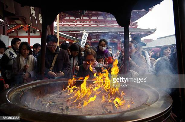 people exposed to the smoke of incense burner - new year's day stock pictures, royalty-free photos & images