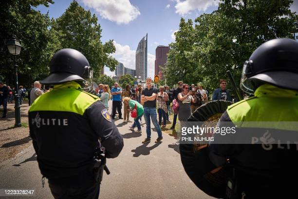 People face riot police officers as they demonstrate against the government's measures taken to stop the spread of the Covid-19 disease caused by the...