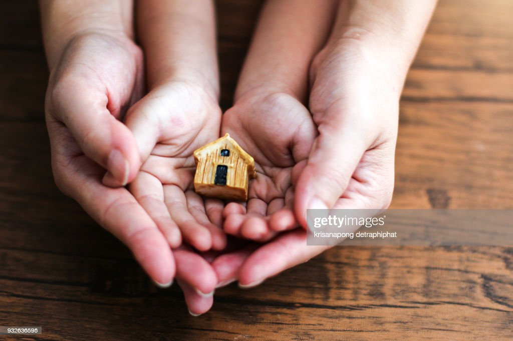 people, family and home concept - close up of woman and girl holding model house : Stock Photo