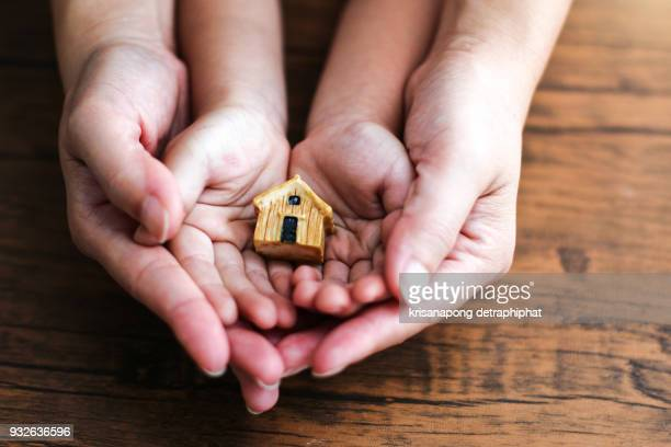 people, family and home concept - close up of woman and girl holding model house - home insurance stock pictures, royalty-free photos & images