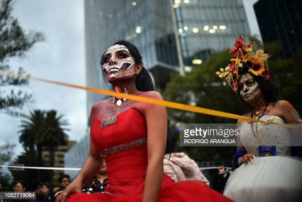 People fancy dressed as Catrina take part in the Catrinas Parade along Reforma Avenue in Mexico City on October 21 2018 Mexicans get ready to...