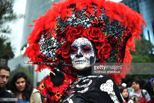 TOPSHOT People fancy dressed as Catrina take part in the Catrinas Parade along Reforma Avenue in Mexico City on October 21 2018 Mexicans get ready to...
