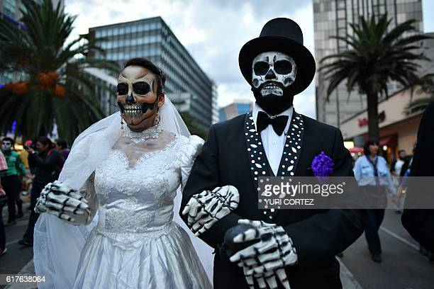People fancy dressed as Catrina take part in the Catrinas Parade along Reforma Avenue in Mexico City on October 23 2016 Mexicans get ready to...