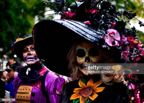 People fancy dressed as Catrina take part in the Catrinas Parade along Reforma Avenue in Mexico City on October 22 2017 Mexicans get ready to...
