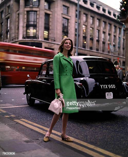 People/ Fashion 1960's An attractive young women wearing a long green jacket holding a pink handbag stands in a London street as a Taxi and a red bus...