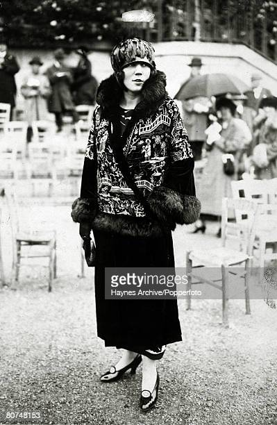 1924 A fashionable lady at Longchamps Paris for the horse racing wearing a coat embroidered with a Japanese design