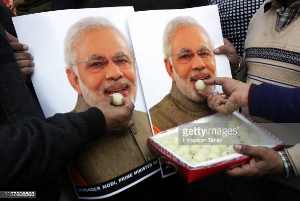 People feed sweets to a poster of Prime Minister Narendra Modi as they celebrate Indians airstrike on the JaisheMohammeds biggest camp in Pakistans...