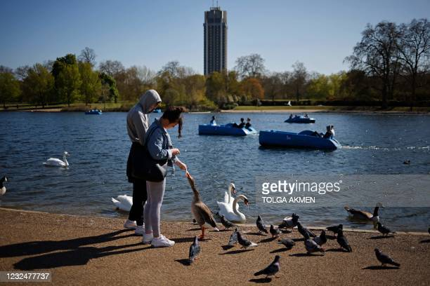 People feed the birds beside the Serpentine in Hyde Park in the Spring sunshine in London on April 23, 2021. - Under the relaxing of the Covid-19...