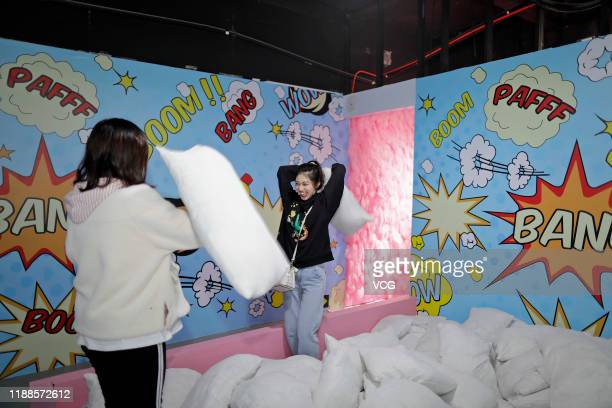 People fight with pillows at a stress-relief museum on November 18, 2019 in Suzhou, Jiangsu Province of China.