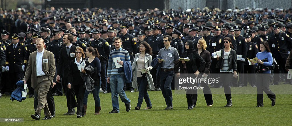People file into the memorial service for MIT police officer Sean Collier, at Briggs Field, on the MIT campus. Collier was killed during a shootout with the Boston Marathon bombing suspects.