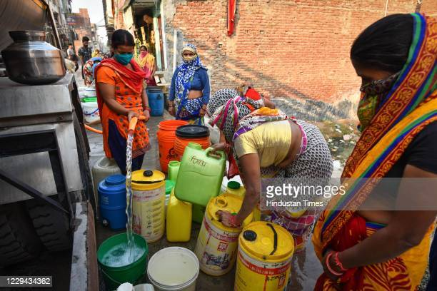 People fill buckets with water from a Delhi Jal Board tanker at Swaroop Nagar, on November 2, 2020 in New Delhi, India.