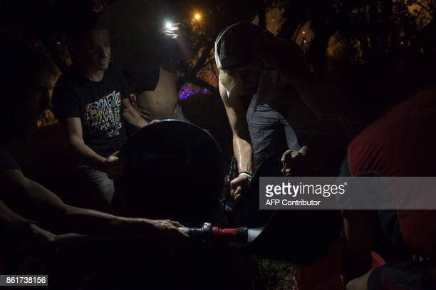 People fill buckets with water to help fighting a wildfire in Vigo northwestern Spain on October 15 2017 Hundreds of firefighters struggled on...