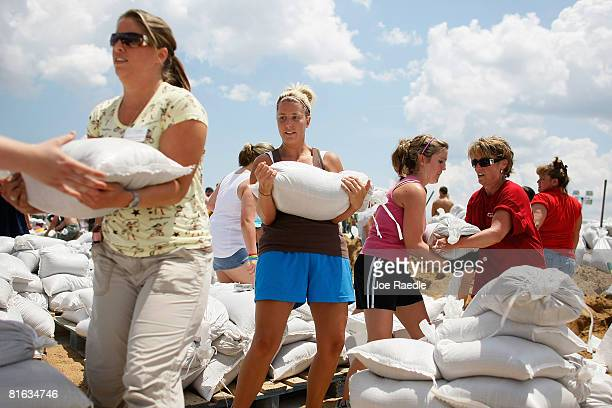 People fill sandbags to be used in supporting a levee against the flood from the Mississippi River June 19, 2008 in Winfield, Missouri. Towns along...